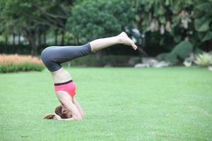 mujer joven en pose de yoga headstand en césped foto