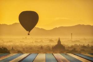 Balloons over Buddhist temples at sunrise in Bagan, Myanmar.