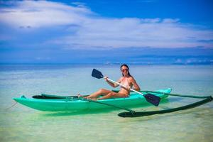 Young woman kayaking alone in the clear blue sea photo