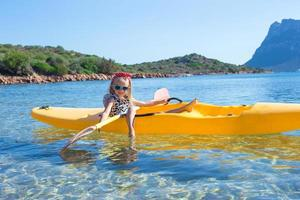 Little happy girl kayaking in blue sea during summer vacation photo