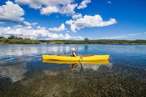 Río tranquilo y mujer relajante en un kayak