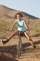 Woman on bicycle in desert landscape photo