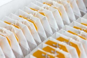 Yellow tagged teabags packed in a row. photo
