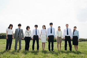 Businesspeople in a row in field, holding hands photo