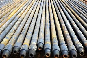 A row of long dirty steel drill pipes