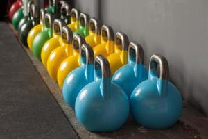 colorful kettlebells in a row in a gym photo