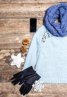 Winter clothes on wooden background.