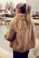 girl with blond hair wearing luxurious fur coat photo