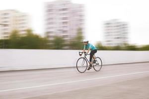 young female athlete racing on a bike. motion blurred image photo