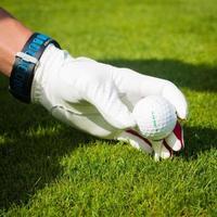 mano sostenga la pelota de golf con tee en curso, de cerca foto