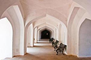 Silla en pasillo vacío con pilares tallados a mano en un abandonado
