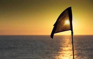 bandera del campo de golf en silueta en la puesta del sol foto