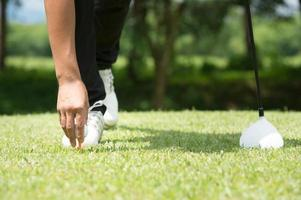 golfista colocando la pelota de golf en tee foto