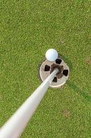 Aerial view of golf ball near pin and hole golf