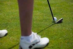 Golf ball on tee and golf club on golf course photo