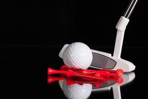 Putter de golf y equipos dorados en el escritorio de cristal negro foto