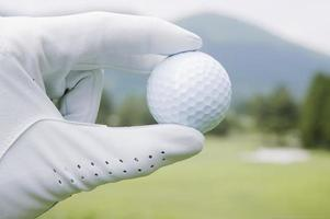 Golf ball being held by gloved hand, close-up photo