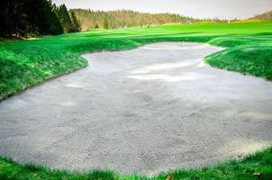 Búnker de arena en el campo de golf. trampa de arena foto