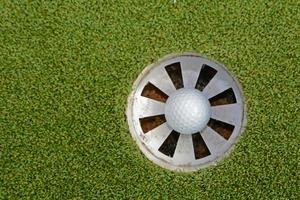 Golf ball staying in the hole photo