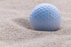 Close up golf ball in sand bunker . photo