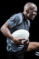 agressieve sportman met bal tijdens het spelen van rugby