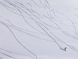 Snowboarder downhill on off piste slope with newly-fallen snow photo