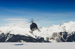 A mountain rescue helicopter in flight by snowy mountains