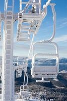 Frozen chair lift at snow resort in winter mountains