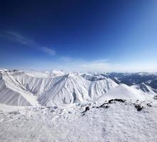 Winter snowy mountains and blue sky photo