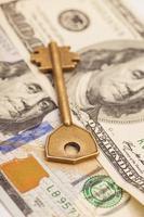 Closeup of key on hundred dollar bills photo