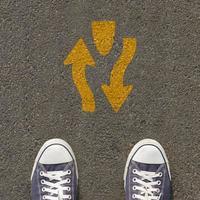 par de sapatos em pé em uma estrada com sinalização de trânsito