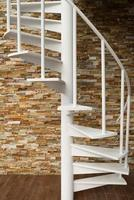 White spiral staircase on stone wall