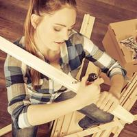 Woman moving into apartment assembly furniture. photo