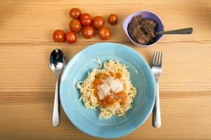 Place setting for a child with pasta and tomatoes photo