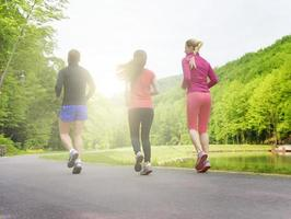 Smiling friends running outdoors photo