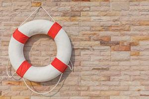 The life buoy is hanged on brick wall background. photo