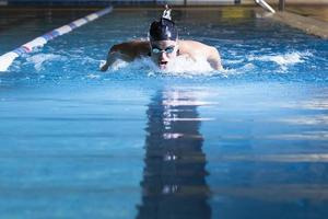 young woman swimming butterfly stroke photo