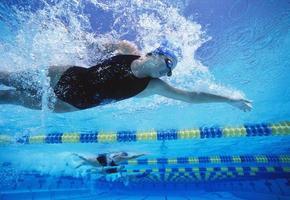 Nadadoras profesionales que nadan en la piscina foto