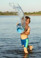 little boy throwing water from bucket at river photo