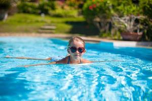 Little adorable happy girl swim in the swimming pool photo
