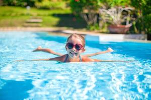 Little adorable happy girl swims in the swimming pool photo