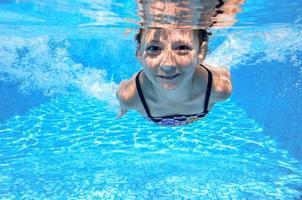 Happy active underwater child swims in pool photo