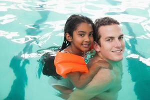 Cute little girl learning to swim with coach photo