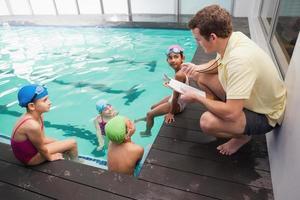 linda clase de natación escuchando entrenador foto
