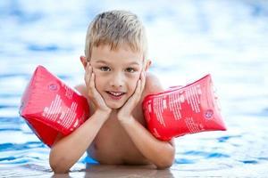 niño con alas de agua en la piscina foto
