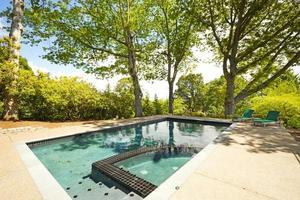 piscina de quintal com cadeiras e sombras de árvores