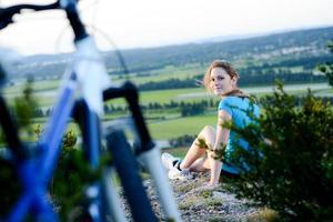 gesunde fröhliche junge Frau, die Fahrrad reizenden schönen Landschaftshintergrund fährt