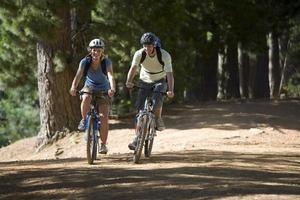 Couple, with rucksacks and cycling helmets, biking along woodlan