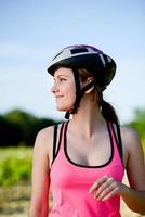 gesunde fröhliche junge Frau, die Mountainbike im Freien in der Landschaft reitet