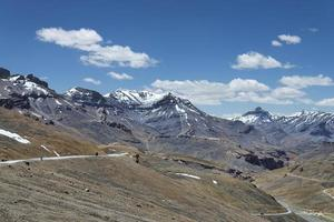 Bike riding by high mountain winding road photo